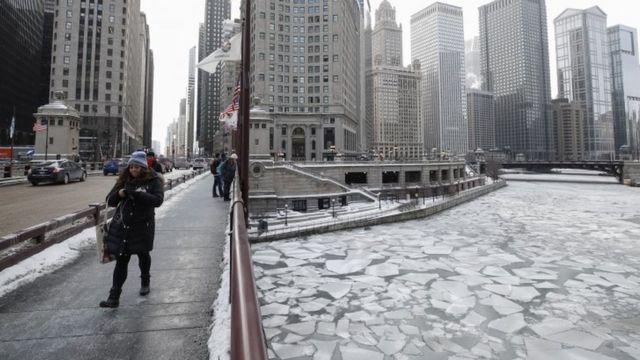 Imagem mostra mulher caminhando e outras pessoas na rua em meio a prédios e à área congelada em Chicago, em meio a intensa onda de frio nos EUA