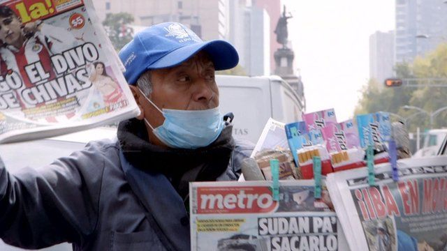Man selling papers while wearing smog mask in Mexico City