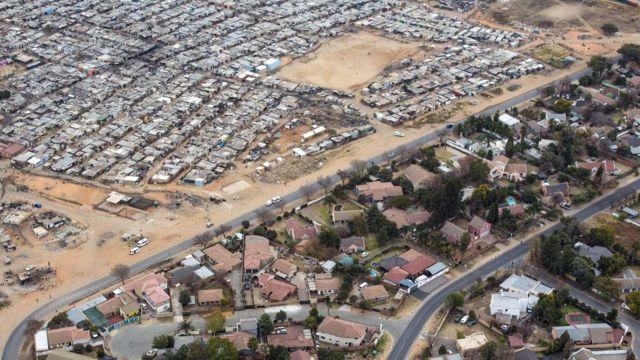 Una carretera divide el barrio de clase media de Bloubusrand, en Johannesburgo, del campo Kya Sands, hogar de muchos inmigrantes.