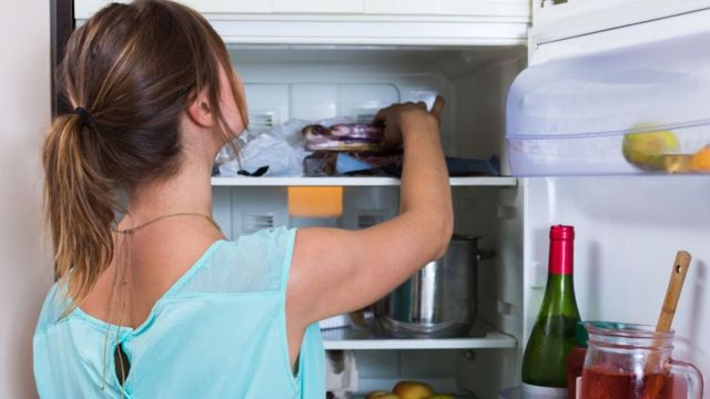 Mulher pegando comida na geladeira