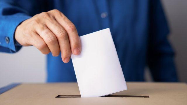 Pessoa colocando voto em urna