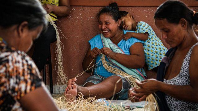 Três mulheres warao fazem artesanato, uma delas tem um grande sorriso e uma criança apoiada no ombro