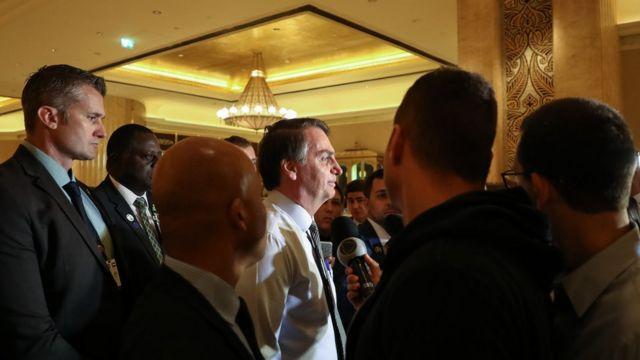 Bolsonaro aparece de perfil falando com jornalistas de dentro de hotel em Abu Dhabi