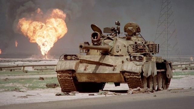 Un tanque abandonado en el desierto de Kuwait con un poso de petróleo en llamas en el fondo.