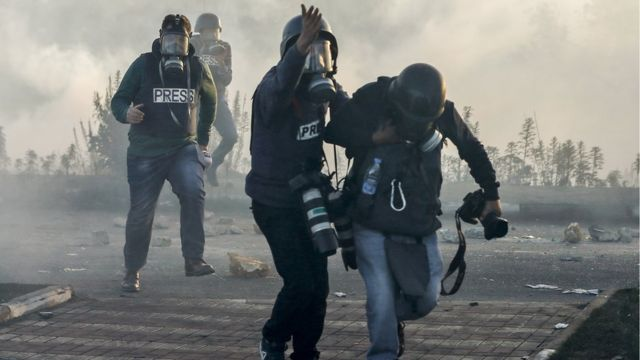 Photojournalists and video journalists wearing gas masks flee from teargas during clashes with Israeli forces near an Israeli checkpoint in the West Bank city of Ramallah.