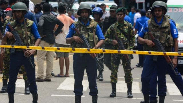 Sri Lankan military officers stand guard outside church after attack