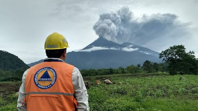 Un empleado de emergencias mira al Volcán de Fuego