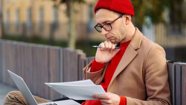Un hombre con una computadora y un bolígrafo en la mano pensando.