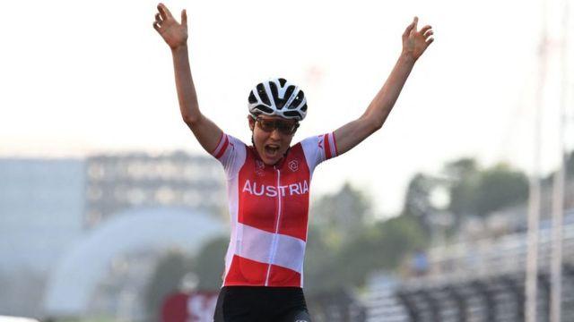 Anna Kiesenhofer, de Austria, levanta los brazos al ganar la prueba de ciclismo de ruta en Tokyo 2020