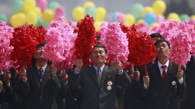 مجموعة من الرجال يرفعون أكاليل من الزهور الاصطناعية المخصصة للزينة.