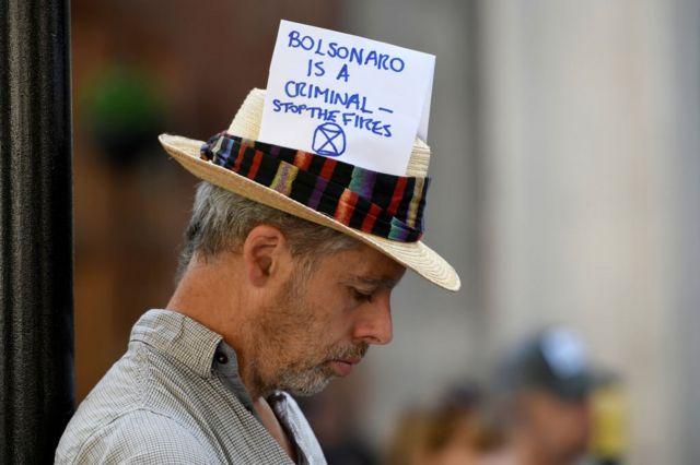 'Bolsonaro é um criminoso — Parem os incêndios', afirma mensagem no chapéu de ativista durante protesto na Embaixada do Brasil em Londres, em 2019