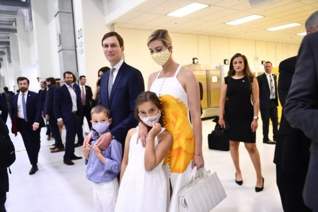 An unmasked Jared Kushner alongside a masked Ivanka Trump and their kids during a public appearance