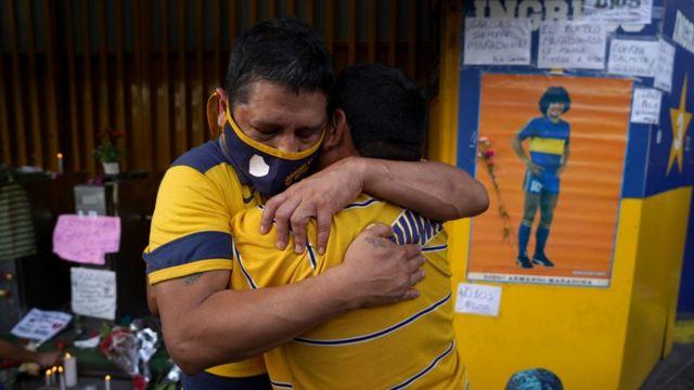 Seguidores se abrazan por la muerte de Diego Maradona.