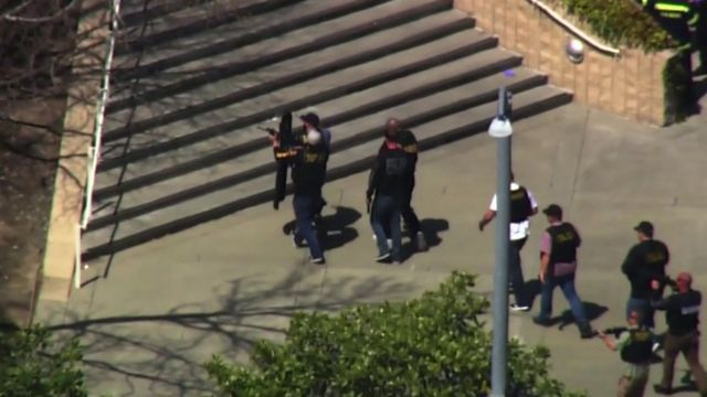 Police with guns drawn seen outside the YouTube building