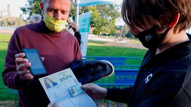 Homem mostra passaporte da imunidade em Israel