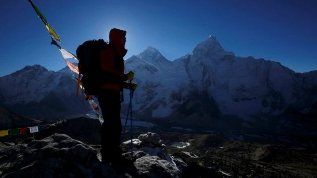 A hiker is seen in side-on silhouette on Everest
