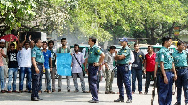 Students protesting on a street in Sylhet, watched by security officers