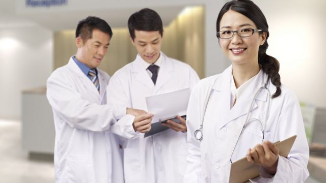 A female Chinese doctor, and two male doctors in the background