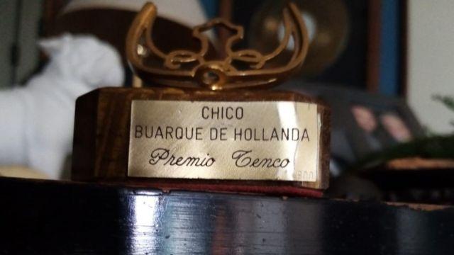 Trofeú em cima da mesa diz: Chico Buarque de Hollanda, troféu Tenco