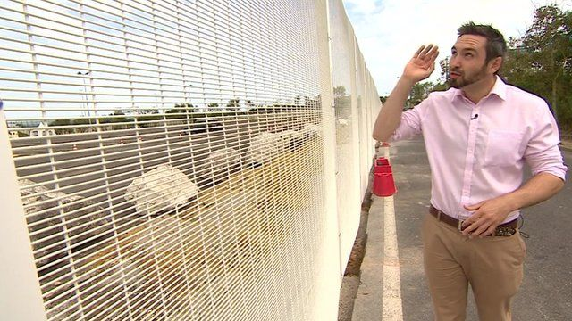 BBC reporter Tomos Morgan at a fence in Calais