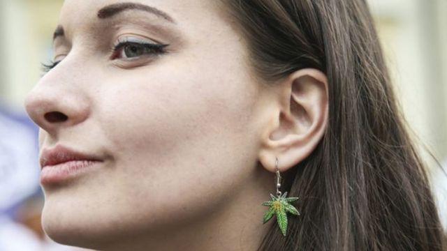 Mulher com brinco em formato de folha de maconha