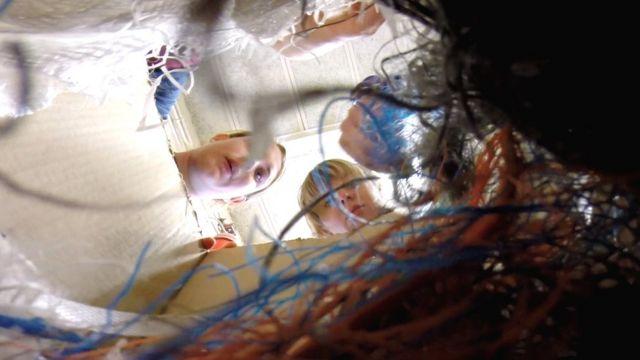 Equipe observa alguns dos itens de plástico coletados pela engenhoca