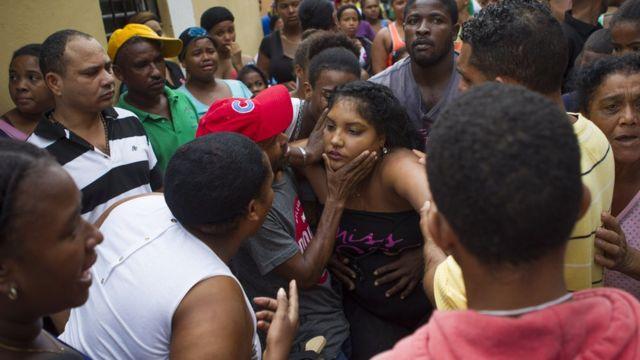 Los vecinos del barrio de Capotillo intentan consolar a la madre de las niñas que murieron cuando un desplazamiento de tierra impactó las paredes de su casa durante el paso del huracán Matthew.