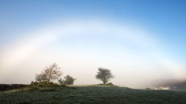 La luz del Sol atravesando una capa de neblina sobre un paisaje rural crea un arco conocido como arcoíris de niebla o arcoíris blanco.
