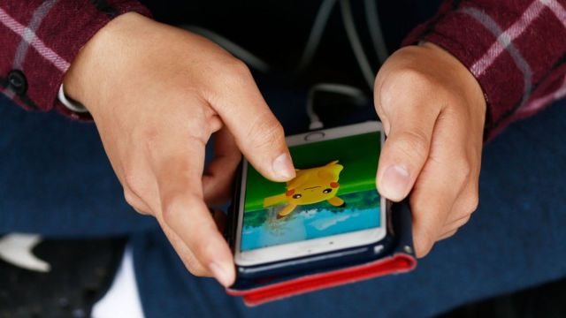 A close-up of someone playing Pokemon Go on their smartphone
