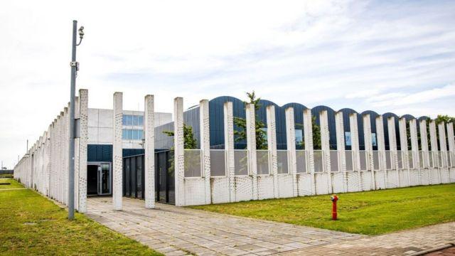 Здание-ангар за бетонным частоколом