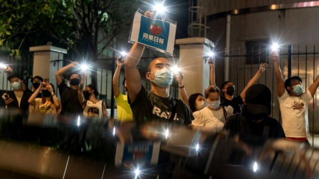 Supporters hold up placards and shine their cellphone torch outside of the Apple Daily newspaper offices