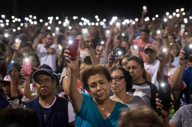 People hold up their phones during a prayer vigil