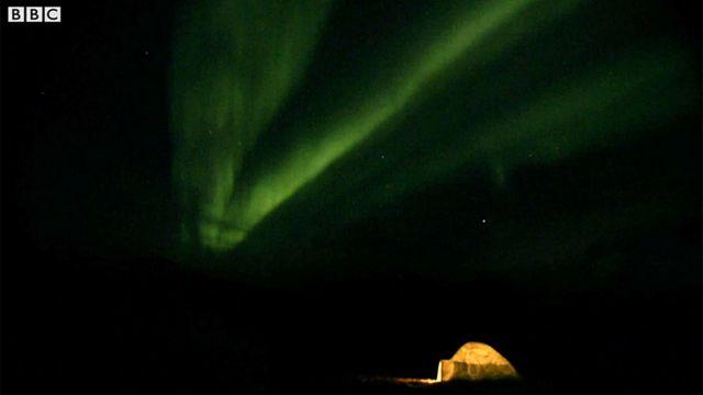 Un domo iluminado en medio de una oscuridad alumbrada por las luces de la aurora boreal.