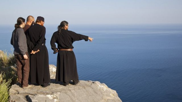 Monges e peregrinos observam a vista de Monte Athos, na Grécia