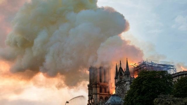 A firefighter uses a hose to douse flames billowing from the roof at Notre-Dame Cathedral