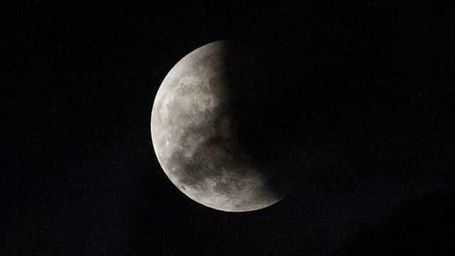 A lunar eclipse is partially seen from The Avenue of Stars in Hong Kong on October 8, 2014. The total lunar eclipse is the second of two in 2014 and the second in a tetrad (four total lunar eclipses in series).