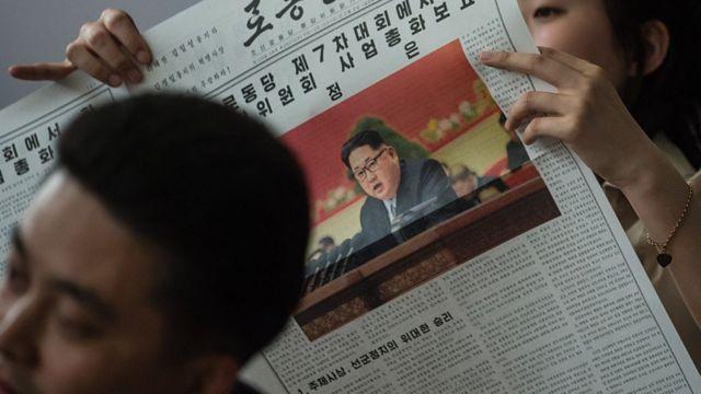 Norcoreanos leyendo un periódico en Corea del Norte, con la foto de Kim Jong-un en la portada.