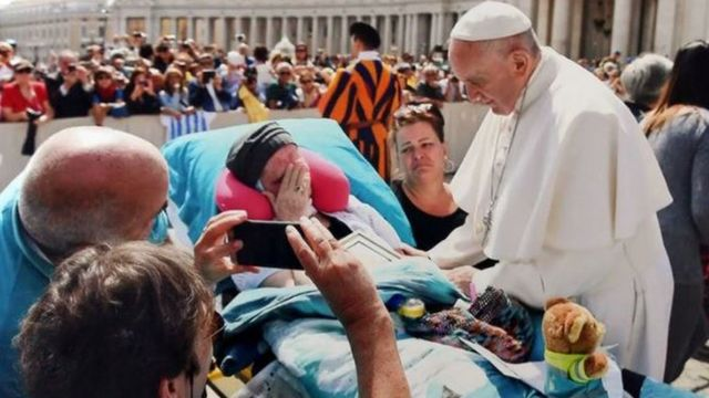 Pope Francis blessing a terminally ill patient
