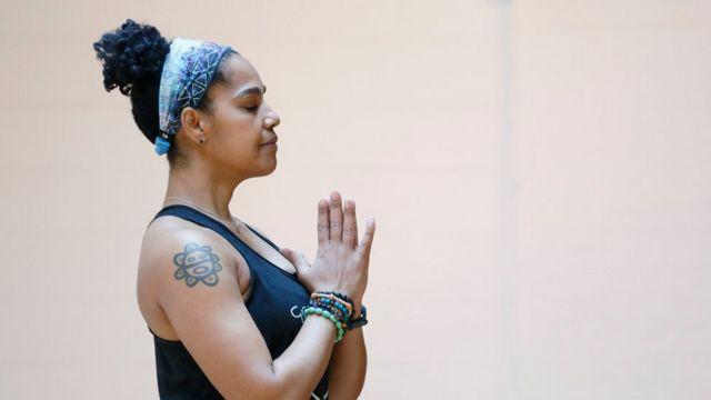 Mujer meditando con las manos en posición de rezo