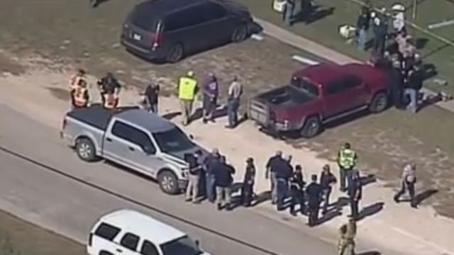 Aerial shot of people milling around scene of shooting