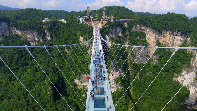 Aerial view photo shows tourists visiting on the glass-bottom bridge at Zhangjiajie Grand Canyon on August 20, 2016