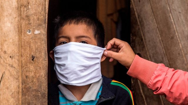 Una madre coloca una mascarilla en un niño en Perú