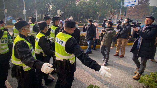 Η αστυνομία σταματά τους δημοσιογράφους μπροστά σε ένα δικαστήριο στη Σαγκάη.