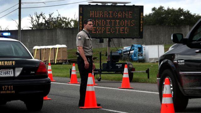Policial americano em barreira montada para orientar moradores