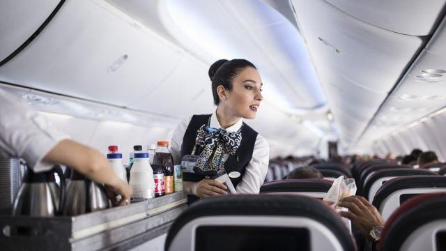 Comissária de bordo atende passageiros