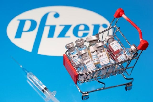 """A small shopping basket filled with vials labeled """"COVID-19 - Coronavirus Vaccine"""" and a medical sryinge are placed on a Pfizer logo"""