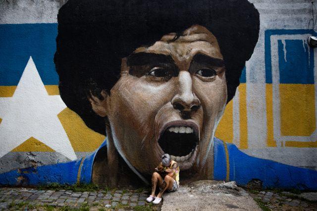 म्यराडोनाको भित्तेचित्रअगाडि रुदै गरेकी एक महिला
