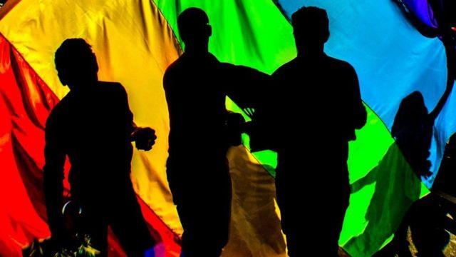 Люди, танцующие на фоне радужного флага