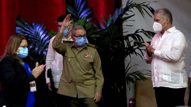 Raul acena, rodeado por mais três pessoas, todas de máscara dentro de sala
