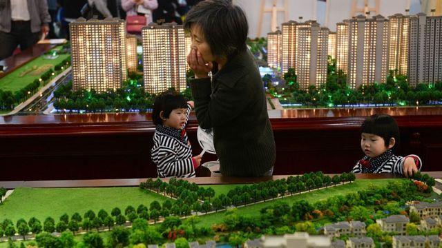 Mulher com os filhos em feira imobiliária na China